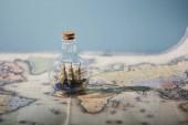 Szelektív összpontosít, játék hajó üvegben és másol hely elszigetelt kék térképen