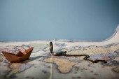 Selective focus of map, compass and paper boat with copy space isolated on blue