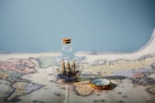 Selective focus of toy ship in glass bottle, map and compass with copy space isolated on blue
