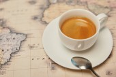 Fotografie Selective focus of world map and coffee cup with spoon on saucer