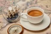 šálek kávy, kompas a hračky loď v láhvi skla na mapě světa