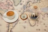 Selektivní fokus kávy šálek a talířek, kompas a hračka lodi v láhvi skla na mapě