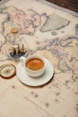 Photo coffee cup and saucer, compass and toy ship in glass bottle on map