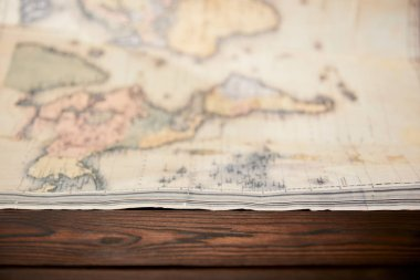 Selective focus of world map on wooden table