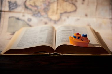 Selective focus of toy ship, book and map on table