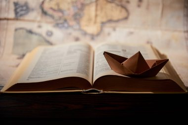 Selective focus of paper boat, book and map on table