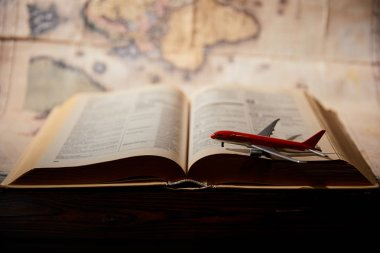 Selective focus of toy plane, book and map on table