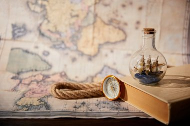 Selective focus of toy ship in glass bottle, book, map, compass and rope stock vector