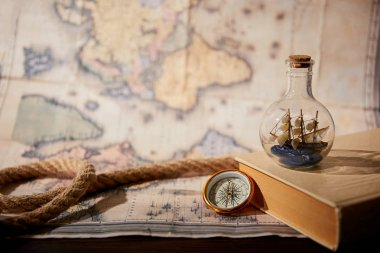 Selective focus of toy ship in glass bottle, book, map and rope on table