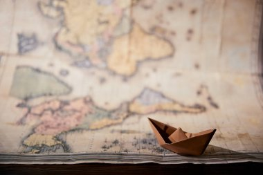 Selective focus of map and paper boat on wooden table