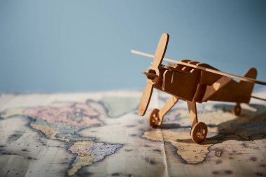 Selective focus of toy plane and map with copy space on blue background
