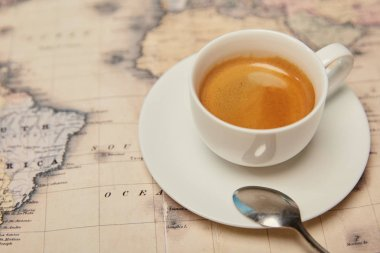 Selective focus of world map and coffee cup with spoon on saucer