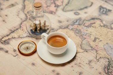 selective focus of coffee cup, compass and toy ship in glass bottle on map