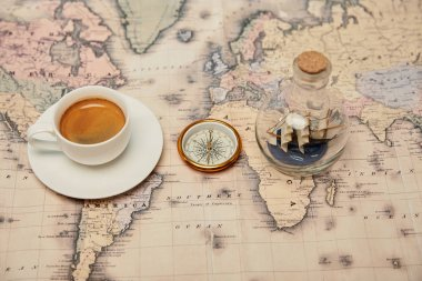 Selective focus of coffee cup and saucer, compass and toy ship in glass bottle on map stock vector