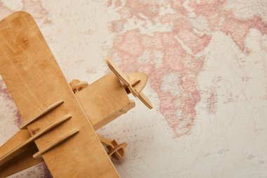 Top view of toy wooden plane on vintage world map
