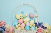 Top view of easter chicken and quail eggs in straw basket and flowers