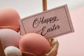 Fotografie Nahaufnahme von Ostern Huhn und Wachtelei, Karte mit happy Easter-Schriftzug