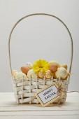 Velikonoční kuře a Křepelčí vejce proutěný koš s květinou a kartu s nápisem šťastné Velikonoce na stole