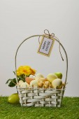 Photo easter chicken and quail eggs in straw basket with flower and card with happy easter lettering on grass