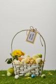 Fotografie Ostern Huhn und Wachteln Eier im Stroh Korb mit Blumen und Karte mit happy Easter Schriftzug auf dem Rasen