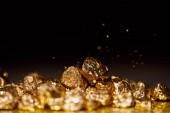 zlaté kameny na šumivé povrchu a černé pozadí