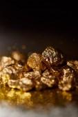 Selektivní fokus zlatých kamenů na šumivé povrchu a černé pozadí.