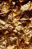 zmačkaný zlaté fólie list s jasně twinkles a stíny