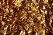 Draufsicht auf zerknüllte Goldfolie mit grellen Augen