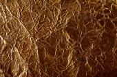 Fotografie top view of rumpled sheet golden foil in shadow