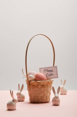 Easter chicken and quail egg in straw basket, card with happy easter lettering and toy rabbits stock vector