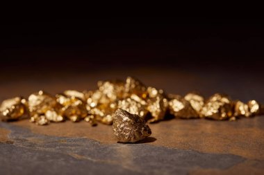 selective focus of golden stones on marble and black blurred background