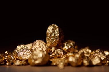 selective focus of golden stones on marble isolated on black