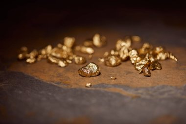 selective focus of golden stones on grey and brown marble surface with blurred dark background