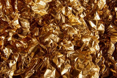 top view of crumpled golden foil with glares