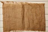 Fotografie kus hnědé pytloviny na bílý dřevěný povrch