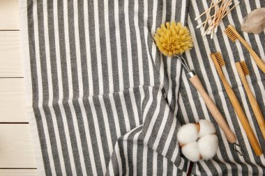 top view of hygiene and care items on striped towel on white wooden surface, zero waste concept