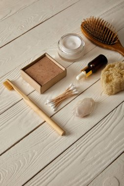flat lay of various hygiene and care items on white wooden surface, zero waste concept