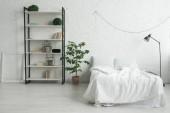 Interiéru útulnou ložnici s polštáře na postel, noční stolek, lampa, rámeček obrázku a stojan