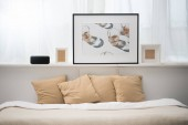 Photo bedroom with brown pillows on bed, alarm clock, picture and photo frames
