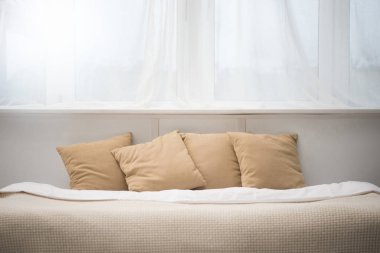 bedroom with brown pillows and white blanket on empty bed