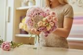 Fotografie částečný pohled květinář aby kytici růží a pivoněk na pracovišti