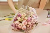 květinářství, kytice z růží a pivoněk zalamuje do pracovního prostoru