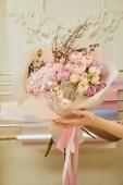 oříznutý pohled květinářství v prostoru drží kytici růží a pivoněk