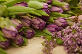 Fotografie  purple tulips and lilac on table at flower shop