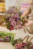 Fotografie oříznutý pohled ženy dělat kytici tulipánů, pivoňky a lila na pracovišti