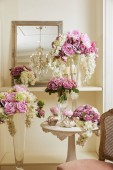 Photo Interior of room with chair, mirror, flowers in vases