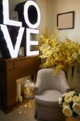 Interior of room with armchair, lighting with love lettering and yellow flowers
