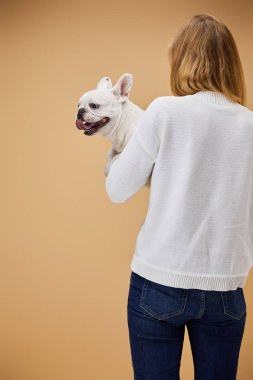 woman in white sweater and blue jeans holding french bulldog on beige background