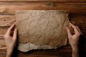 Fotografia cropped view of man holding aged parchment sheet in hands