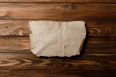Fotografia brown aged parchment sheet on wooden background